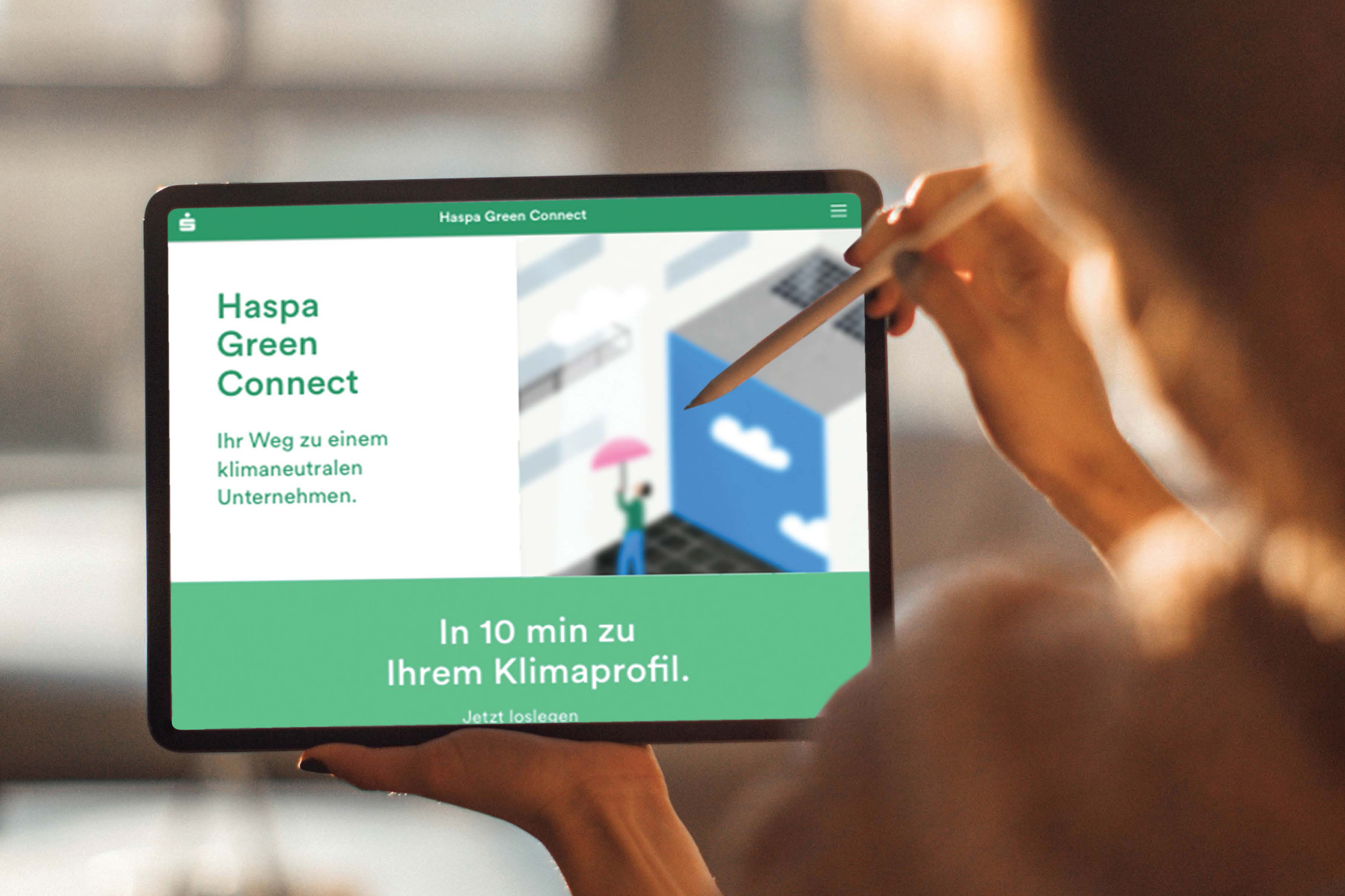Woman holding iPad with HASPA Green Connect app